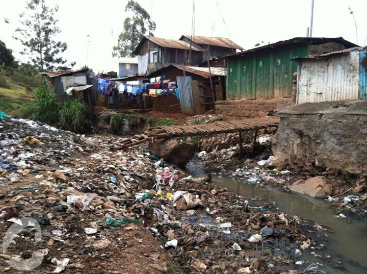 View of Kibera - piles of plastic bags and rubbish next to a row of metal public toilet cubicles.