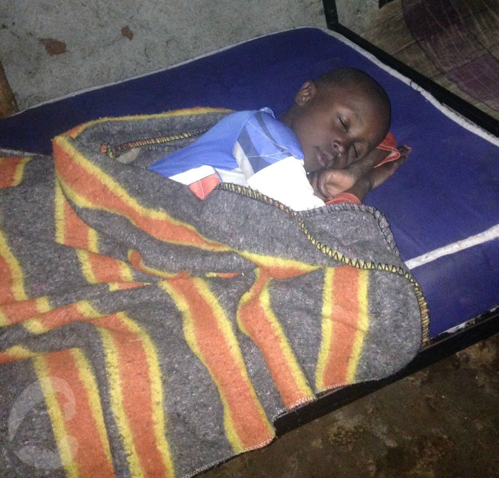 Laurence sleeping in bed at Future Stars after cholera treatment