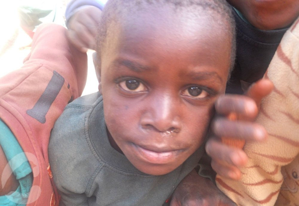 Child looking up at the camera asking for help