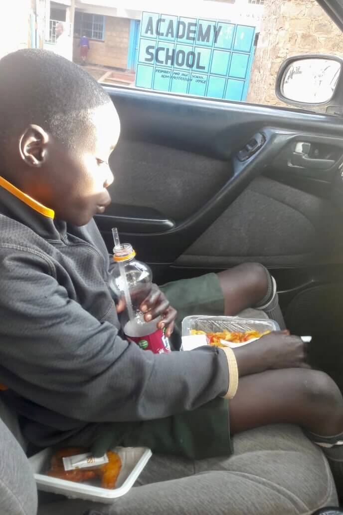 Ibrahim eating a special meal, in the taxi, after his hospital appointment